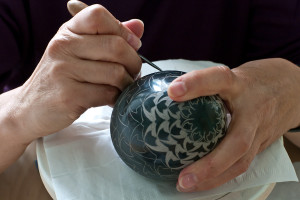 Sgraffitoing on a thrown white clay egg covered with black slip.